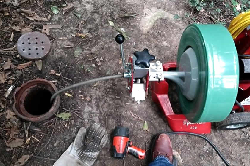 Sewer rodding and drain cleaning equipment being used